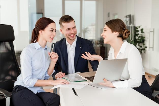 Büroangestellte, die zusammen ein projekt durchführen und über ihre pause in einem modernen firmengebäude lachen Premium Fotos