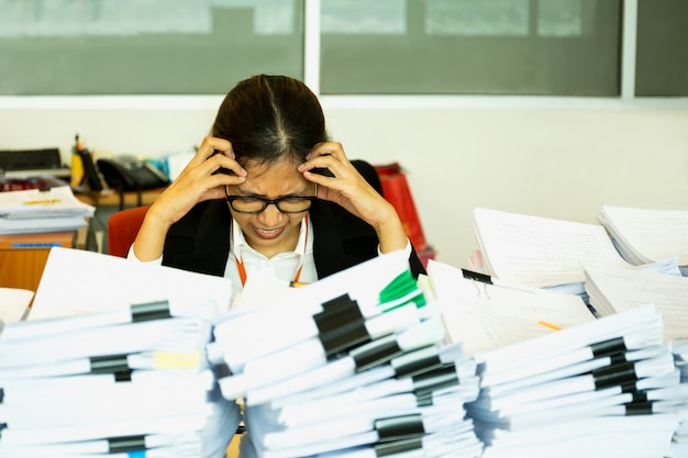 Büroangestellte wird mit viel schreibarbeit auf ihrem schreibtisch beunruhigt. Premium Fotos