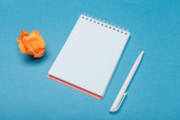 Büroarbeitsplatz mit einem leeren notizbuch, zerknittertes papier Premium Fotos