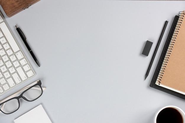 Büroartikel mit tastatur auf grauem schreibtisch Kostenlose Fotos