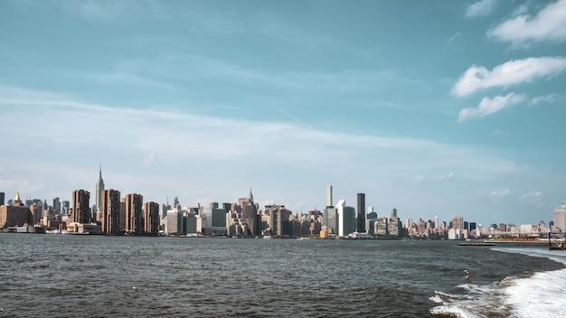 Bürogebäude und wohnungen auf der skyline bei sonnenuntergang, vom hudson river. immobilien- und reisekonzept. manhattan, new york city, usa. Premium Fotos