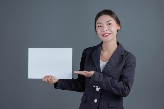Büromädchen, das ein weißes leeres brett hält Kostenlose Fotos
