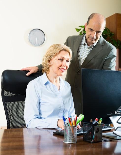 Büroszene mit zwei älteren und positiven arbeitern Kostenlose Fotos