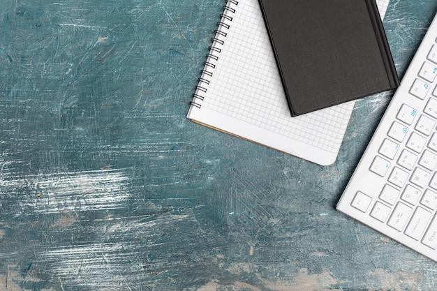Bürotisch mit briefpapier, computertastatur und versorgungen nah oben Premium Fotos