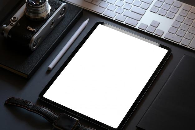 Bürounternehmensmodelldesign mit tablette des leeren bildschirms auf dunklem ledernem schreibtisch Premium Fotos