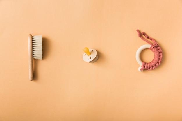 Bürste; schnuller und spielzeug auf einem orangefarbenen hintergrund Kostenlose Fotos