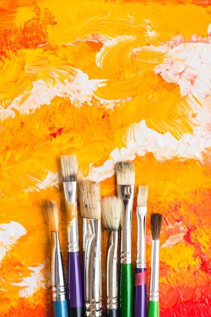 Bürsten, die auf orange malerei liegen Kostenlose Fotos