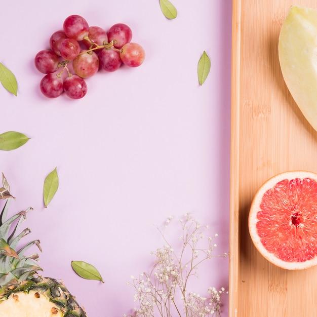 Bund rote trauben; ananas; grapefruit und muskmelon mit gypsophila-blume auf rosa hintergrund Kostenlose Fotos