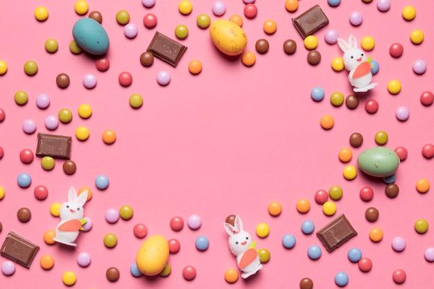 Bunny figur edelstein-bonbons; schokoladen-ostereier mit platz in der mitte auf rosa hintergrund Kostenlose Fotos