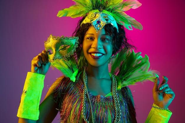 Bunt. schöne junge frau im karneval, stilvolles maskeradenkostüm mit federn, die auf gradientenwand in neon tanzen. konzept der feiertagsfeier, der festlichen zeit, des tanzes, der party, des spaßes. Kostenlose Fotos