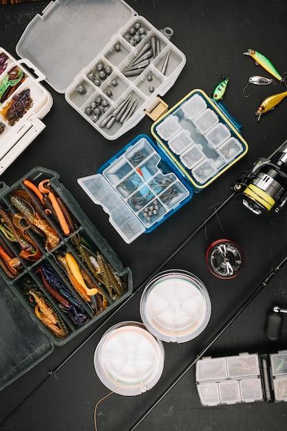 Bunte angelausrüstung mit angelrute auf schwarzem hintergrund Kostenlose Fotos