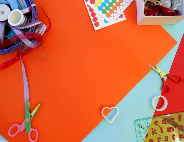 Bunte bänder, box mit fäden, formen, schere und lineal mit buchstaben auf bunten hintergrund Premium Fotos