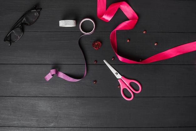 Bunte bänder; schere; perle und schwarze brille auf schwarzem holztisch Kostenlose Fotos