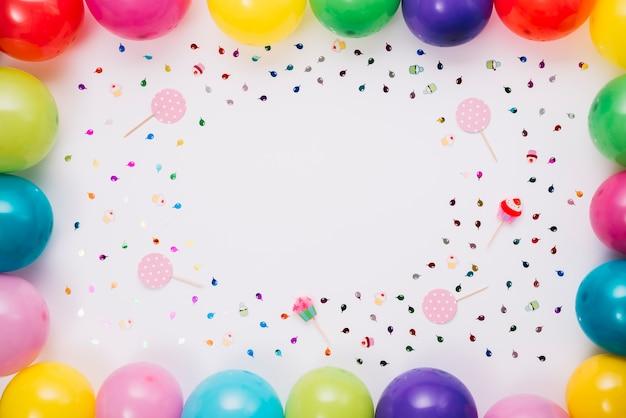 Bunte ballone grenzen mit konfettis und stützen auf weißem hintergrund an Kostenlose Fotos
