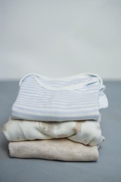 Bunte baumwolle faltete kleidungsstapel auf leerem raumhintergrund der weißen tabelle, babywäscherei. Premium Fotos