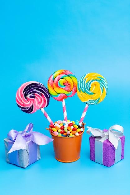 Bunte bonbons der vorderansicht mit regenbogenlutschern und kleinen geschenkboxen auf blau Kostenlose Fotos