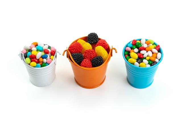 Bunte bonbons der vorderansicht zusammen mit marmeladen auf weißem, farbigem bonbonregenbogen Kostenlose Fotos