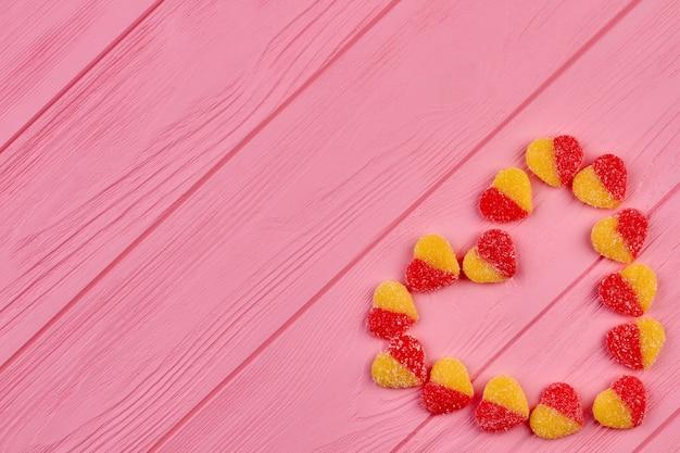 Bunte bonbons, die herzform bilden. herz aus herzförmigen süßigkeiten auf hölzernem hintergrund mit kopienraum. valentinstag-grußkarte. Premium Fotos