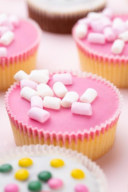 Bunte cupcakes auf einem rosa hintergrund. Premium Fotos