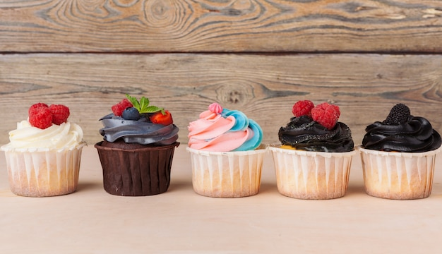Bunte cupcakes mit unterschiedlichen geschmacksrichtungen. kleine schöne kuchen Premium Fotos