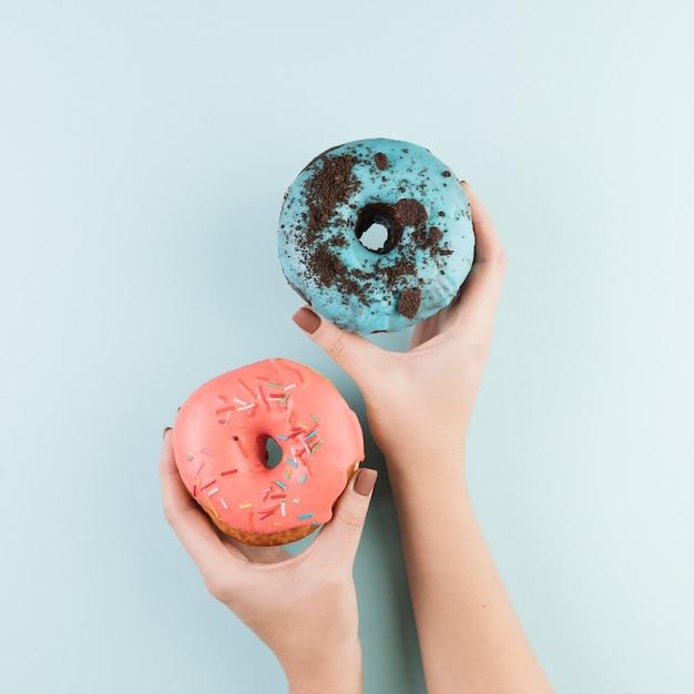 Bunte donuts mit den händen Kostenlose Fotos