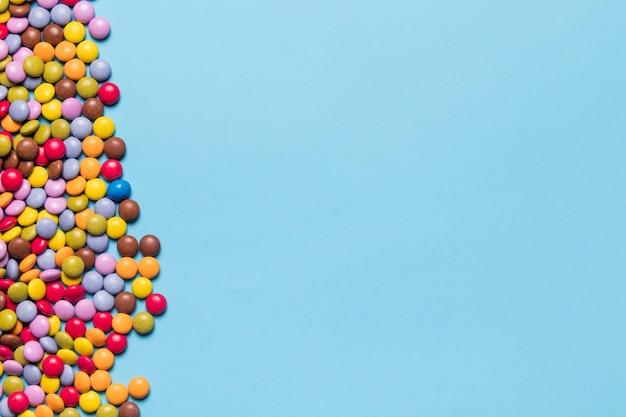 Bunte edelsteinsüßigkeiten auf der seite des blauen hintergrundes Kostenlose Fotos