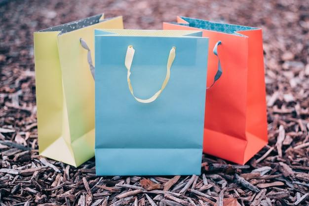 Bunte einkaufstaschen auf dem boden in einem stapel des rohen korkens oder des holzes Premium Fotos