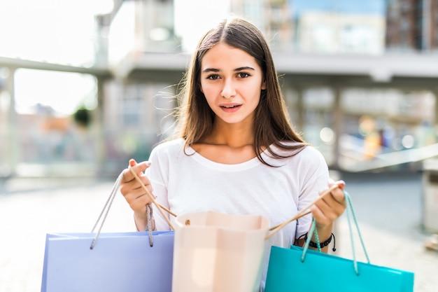 Bunte einkaufstaschen der glücklichen käuferfrau, die sie in die straße zeigen Kostenlose Fotos