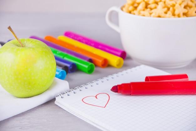 Bunte filzstifte, notizbuch mit skizze, schüssel sternförmiges getreide und apfel auf dem grauen hintergrund Premium Fotos