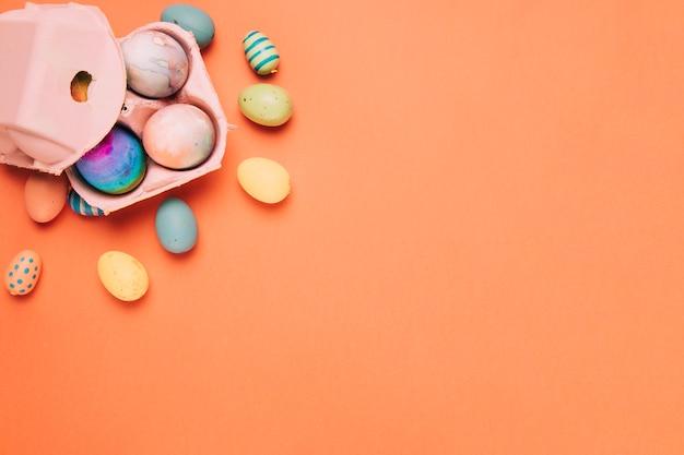 Bunte gemalte ostereier und kartonkasten auf einem orange hintergrund Kostenlose Fotos