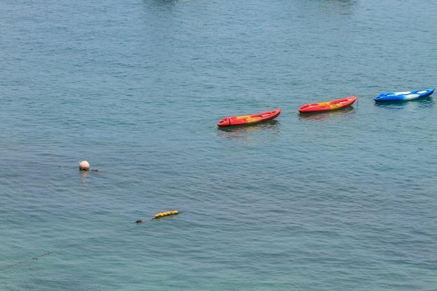 Bunte kajaks, die auf tropisches meer schwimmen Premium Fotos