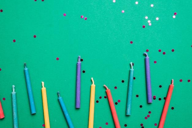 Bunte kerzen mit konfetti auf grünem hintergrund Kostenlose Fotos