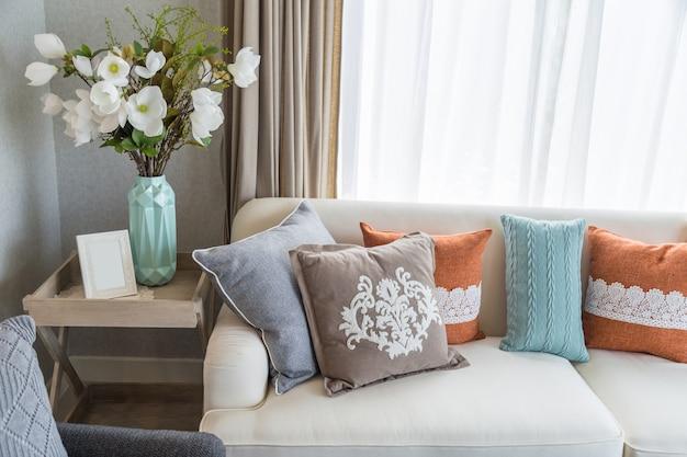 Bunte Kissen auf beige Sofa mit Blumen im Wohnzimmer. | Download der ...