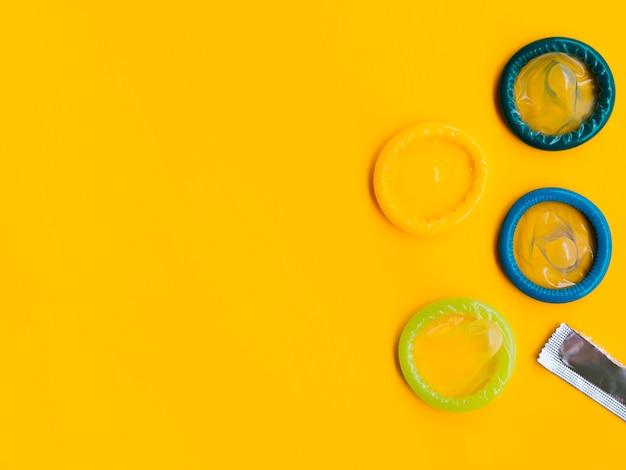 Bunte kondome der flachen lage auf gelbem hintergrund Kostenlose Fotos