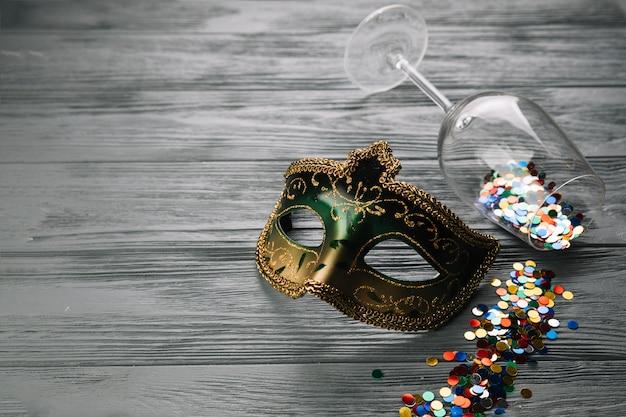Bunte konfettis fielen vom weinglas mit karnevalsmaske auf hölzernem strukturiertem hintergrund Kostenlose Fotos