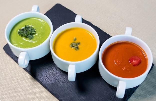 Bunte leckere suppen auf dem schwarzen teller Premium Fotos
