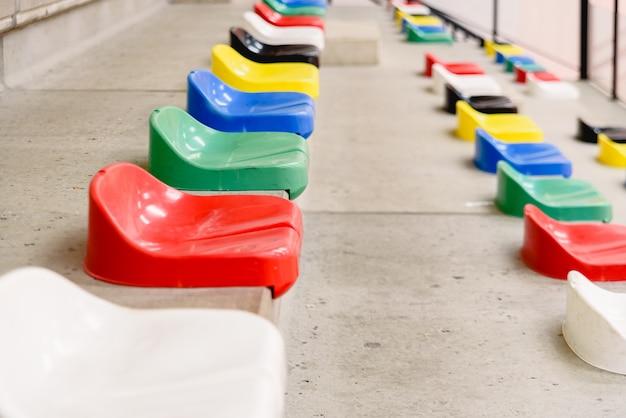 Bunte leere plastiksitze in den ständen eines sportstadions. Premium Fotos