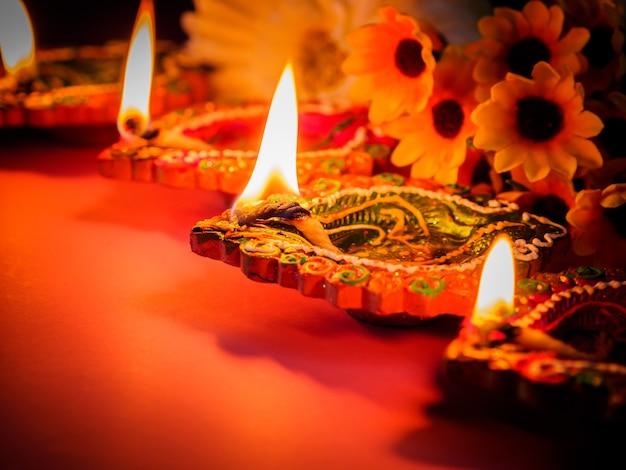 Bunte lehmdiya lampen beleuchteten mit blumen für das hinduistische diwali festival Premium Fotos