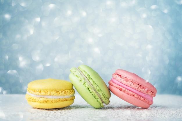 Bunte macarons auf hellblauem glitzer-bokeh-hintergrund Premium Fotos