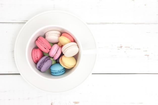 Bunte macarons in einer schale mit dem weinlesepastell gefiltert Premium Fotos