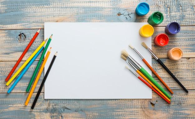 Bunte malereiversorgungen mit weißem leerem papier über hölzernem hintergrund Kostenlose Fotos