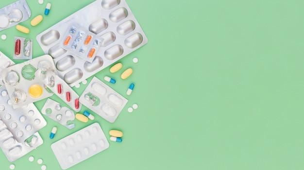Bunte medizinische pillen und splitterblasenpackungen auf grünem hintergrund Kostenlose Fotos