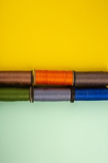 Bunte nähfäden auf einem gelbgrünen schreibtisch Kostenlose Fotos