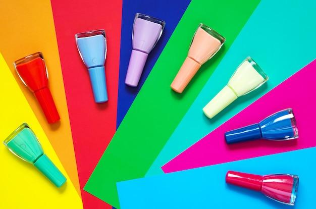 Bunte nagellackflaschen auf multi farbigem papier. Premium Fotos