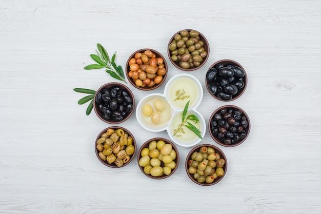 Bunte oliven und olivenöl mit olivenblättern in einem ton und weißen schalen auf weißem holzbrett, draufsicht. Kostenlose Fotos