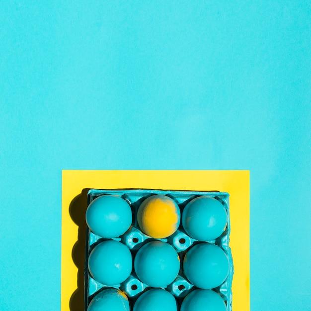 Bunte ostereier im gestell im rahmen auf blauer tabelle Kostenlose Fotos