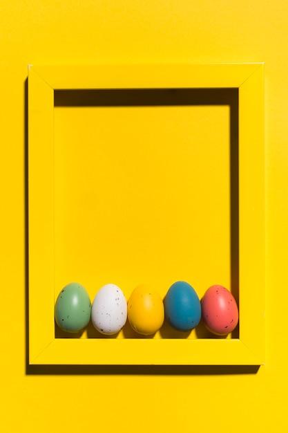 Bunte ostereier im rahmen auf gelber tabelle Kostenlose Fotos