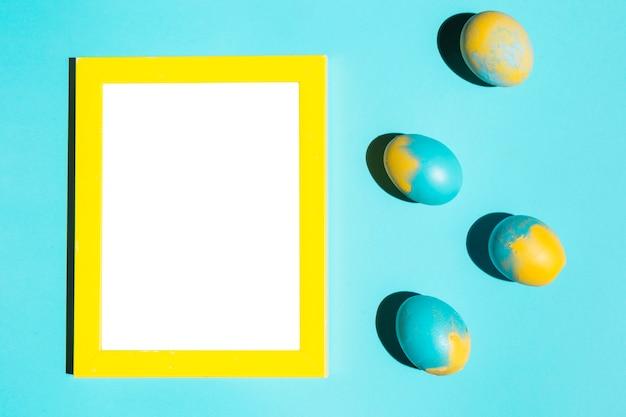 Bunte ostereier mit leerem rahmen auf blauer tabelle Kostenlose Fotos
