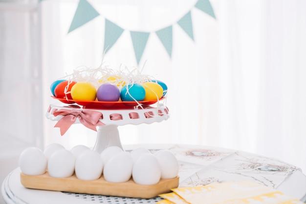 Bunte ostereier mit weißen eiern auf tabelle zu hause Kostenlose Fotos