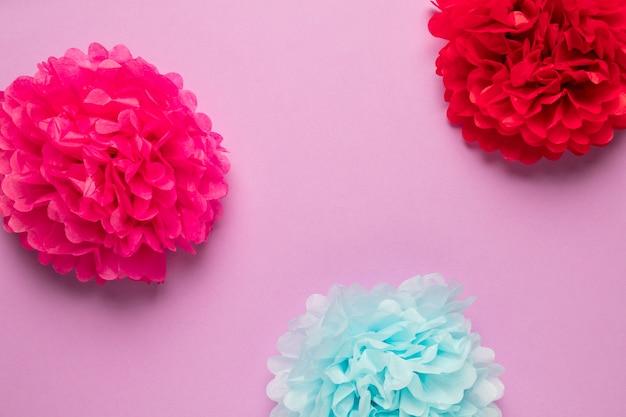 Bunte papierblumen auf rosa hintergrund Kostenlose Fotos